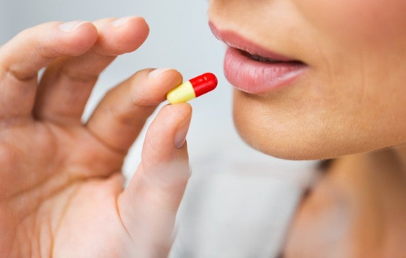 Woman taking an unmarked capsule