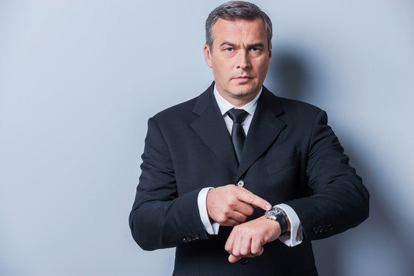Businessman pointing at watch signaling the importance of time.