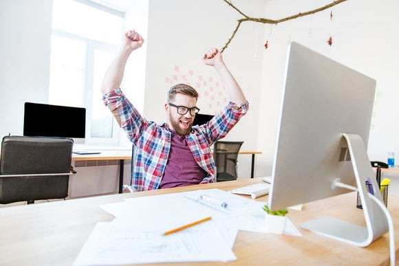 Happy successful man in glasses with raised hands in front of computer at office