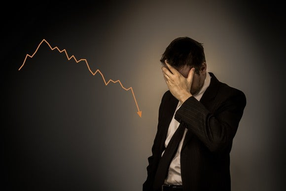 A businessman stands in front of a declining arrow, holding his head in his hands.
