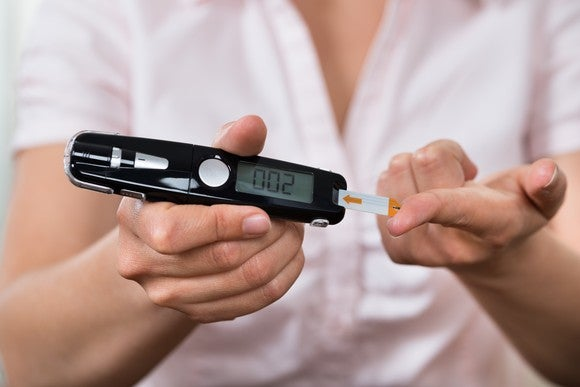 Woman using glucometer to test her blood sugar.