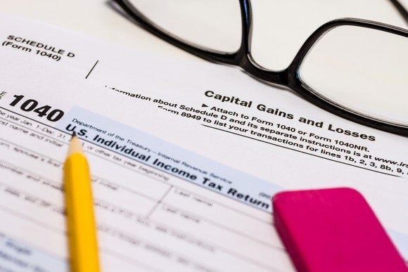 A yellow pencil and pink eraser on top of an IRS Form 1040 and a capital gains tax form.