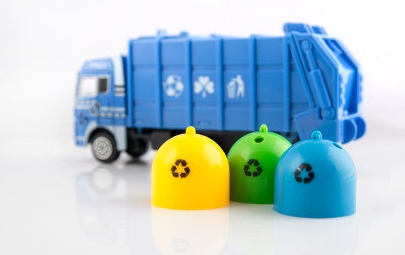 Blue toy garbage truck with three toy recycling bins alongside it
