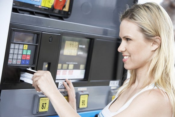 Woman using fuel payment card at pump.