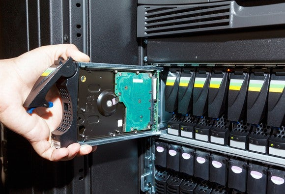 A technician manipulates an enterprise-class hard drive module.