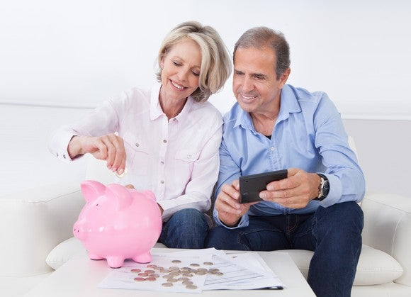 An elderly couple putting money in the piggy bank.