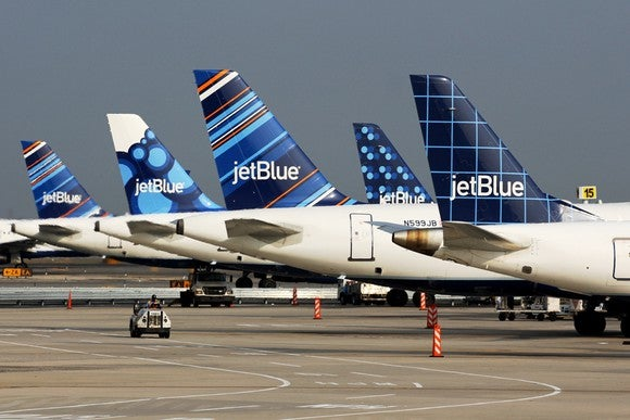The tails of five JetBue planes parked at an airport