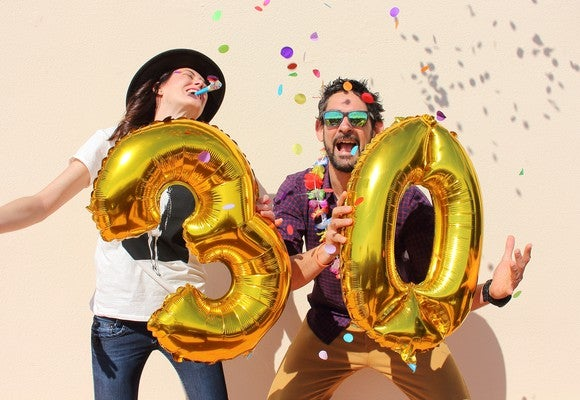 Young couple celebrating with an inflated 3 and 0 - a 30th party