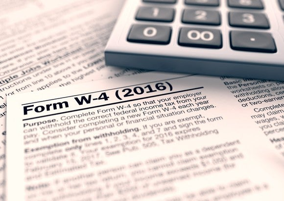 Form W-4 federal tax withholding form sitting next to a calculator.