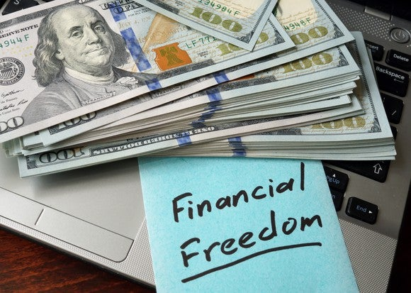 bundles of cash with sign that says financial freedom