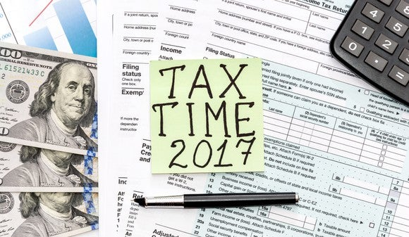"""Tax paperwork, cash, a calculator, and a post it note that says """"Tax Time 2017""""."""