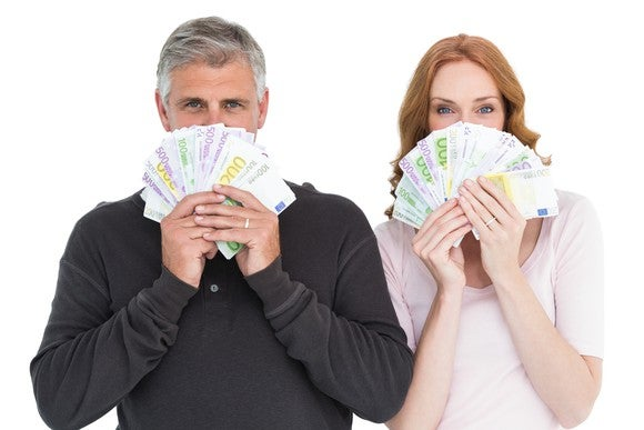 Older couple holding money in front of their faces