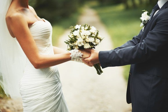 A bride and groom hold a wedding bouquet