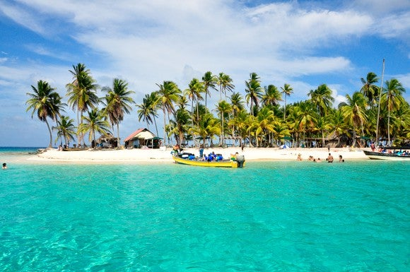 A tropical island surrounded by white sand beaches and blue-green water.