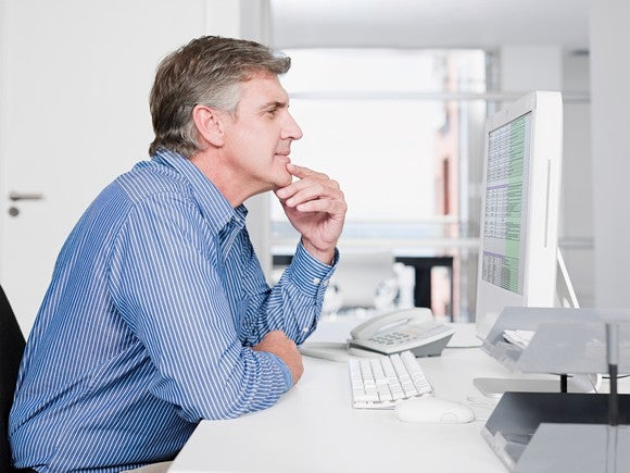 Middle-aged man at desk thinking in front of a computer screen