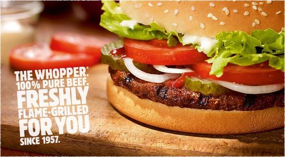 A Burger King Whopper on a cutting board.