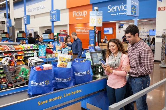A couple using a self-checkout lane at a Wal-Mart supercenter.
