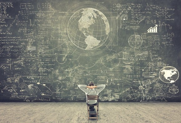 Student sitting in front of a crowded chalkboard.