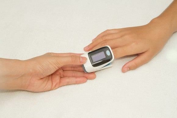 Pulse oximeter on finger with two hands shown
