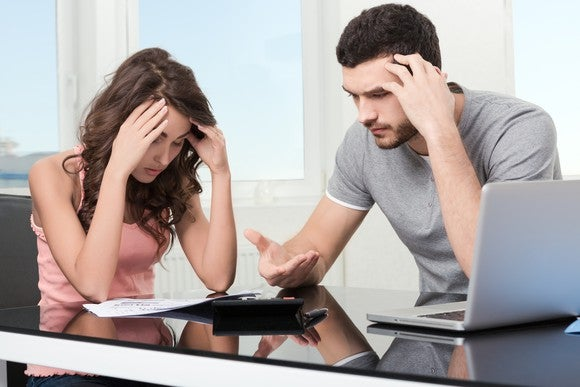 Couple looking over papers, stressed