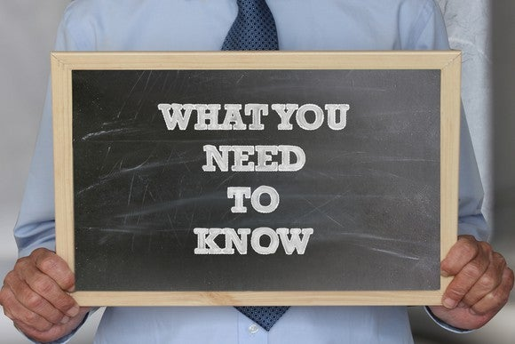 "someone holding a small blackboard on which ""what you need to know"" is written"