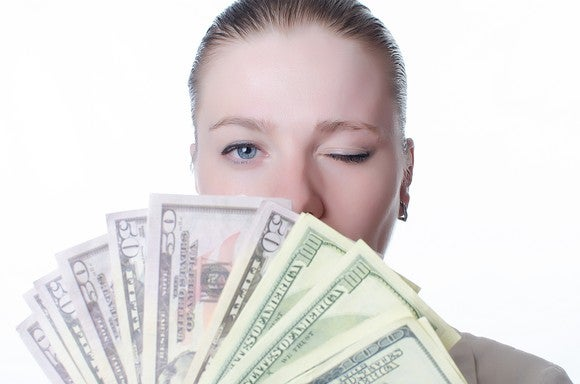 Woman holding lots of cash and winking.