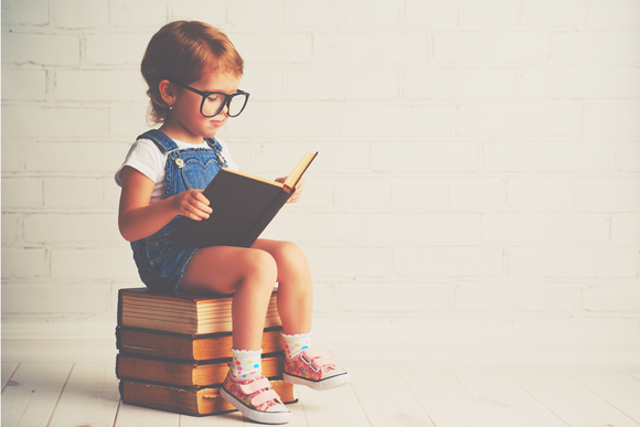 A child sitting on books and reading.