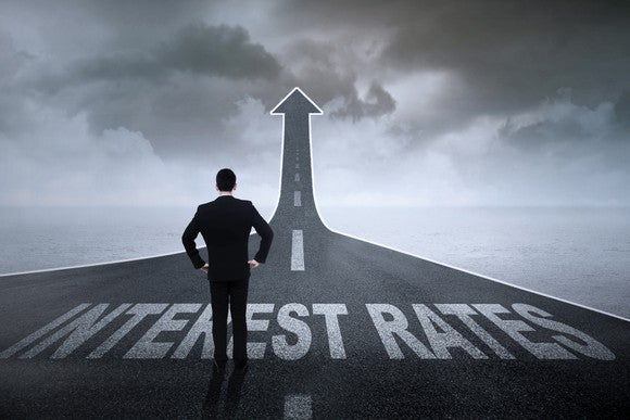 """Businessman contemplating a highway labeled """"interest rates"""" that rises on the horizon."""