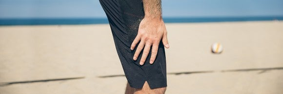 A man wears Lululemon shorts on the beach.
