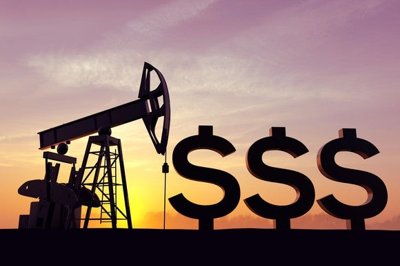 An onshore oil rig operating on a field next to three large dollar signs.