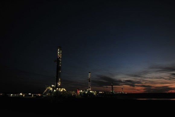 Drilling rigs at an early sunrise.