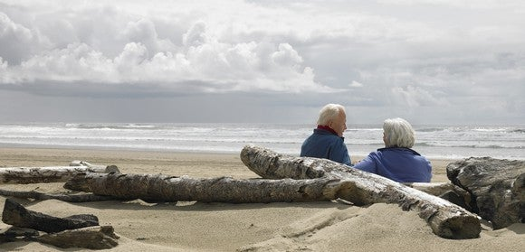 Older couple on a beach with driftwood.