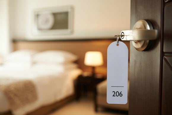 Hotel room key in open door.