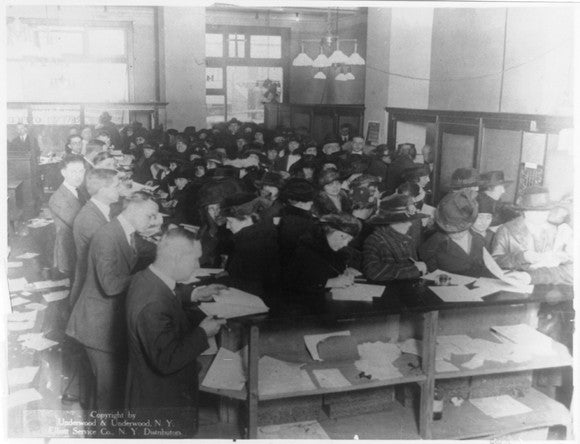People filing taxes in an office in 1920.