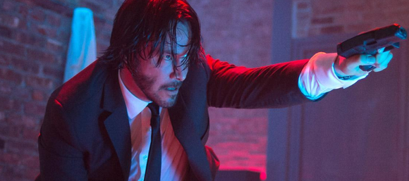 John Wick character points gun at unseen assailant.