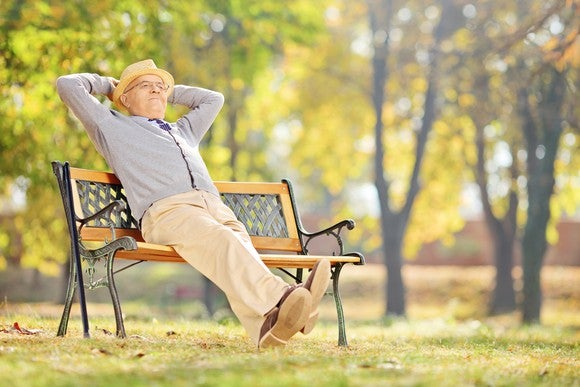 Man on park bench, arms clasped behind his head, happy