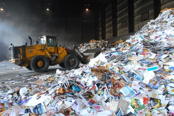 A bulldozer scoops trash from a pile at a Waste Management recycling facility.