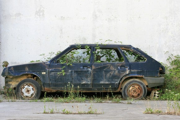 Picture of abandoned car with weeds growing inside of it.