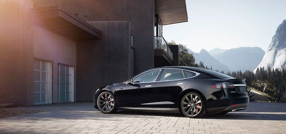 Picture a Tesla Model S sedan parked in the driveway of a house.