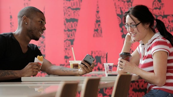A young couple sits in a McDonald's restaurant.