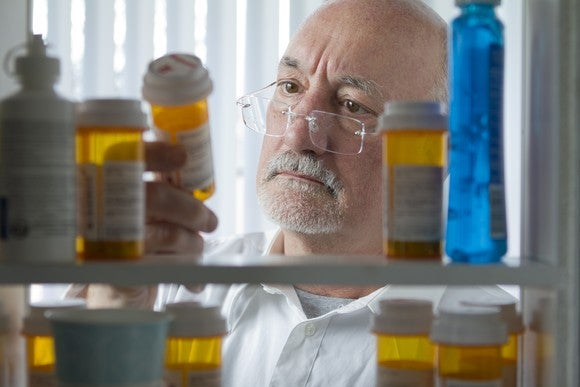 Senior citizen examining pills in his medicine cabinet