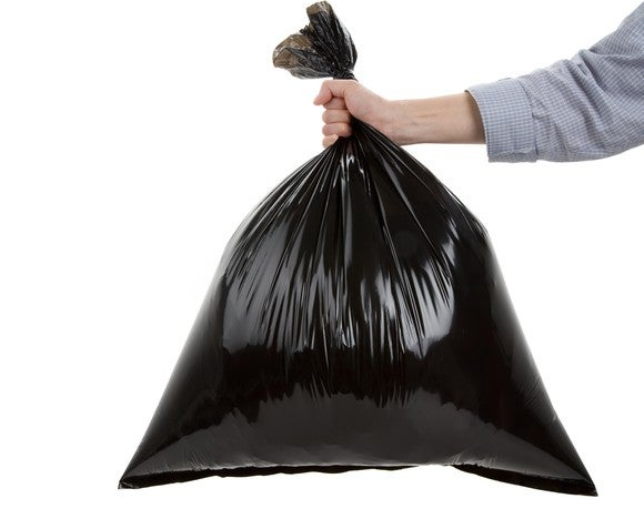 Hand holding black trash bag.