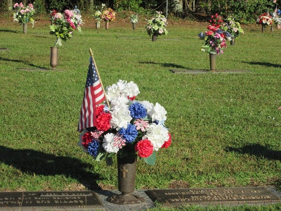 A cemetery with flowers and an American flag on gravestones.
