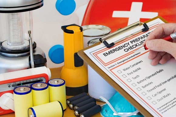 A person fills out an emergency checklist while looking at supplies.