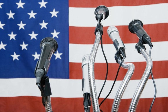 Microphones in front of an American flag - seemingly waiting for a politician to appear and speak