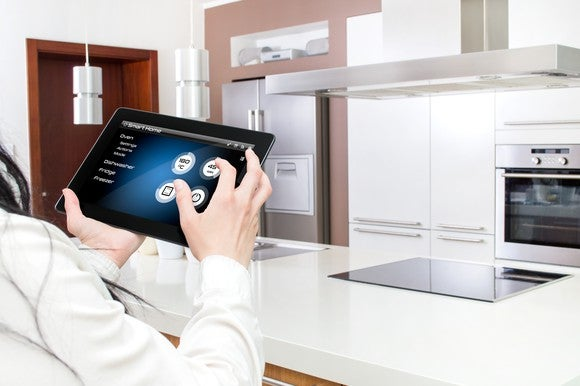 A women controls a smart  kitchen using an iPad.