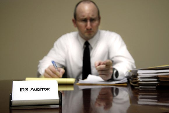 "IRS employee at desk with nameplate that says ""IRS auditor,"" looking mad and pointing at viewer"