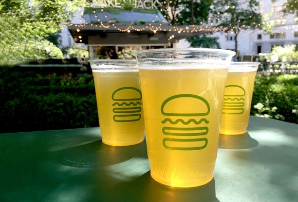 Drinks with the Shake Shack logo in front of a restaurant.