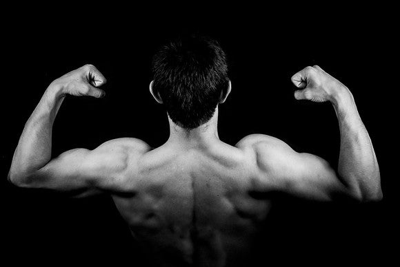 Black and white shot of the back of a man, making muscles, showing off biceps and back muscles