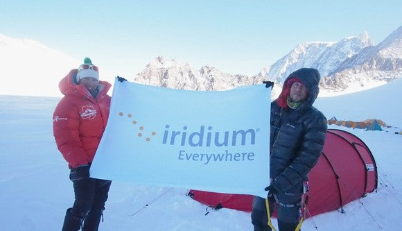 Two people in Arctic conditions holding Iridium sign.
